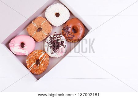 Colorful delicious donuts with coconut and other sprinkles in a box on a white wooden background