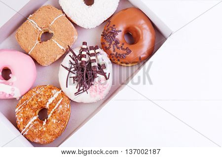 Colorful delicious donuts with coconut and other sprinkles in a box on a wooden background