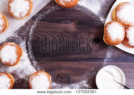 German donuts - berliner with jam and icing sugar on a wooden background. Berliner arranged as frame with copy space. Top view