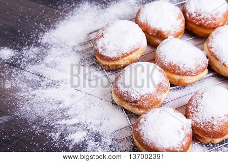 German donuts - berliner with icing sugar on a dark wooden background