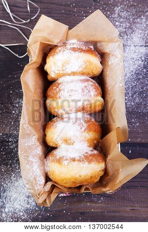German donuts - berliner with jam and icing sugar in a box on a dark wooden background. Top view