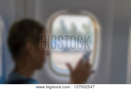 blurry image of Woman's hand holding and using mobile smartphone at airplane