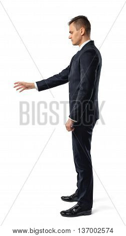 Side view of businessman reaches out to open something, isolated on white background. Successful lifestyle. Business staff. Office clothes. Dress code. Presentable appearance.