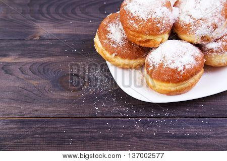 German donuts - berliner with icing sugar on plate on a dark wooden table