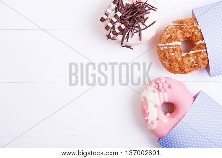 Colorful delicious donuts with chocolate glaze and crispy sprinkles on a white wooden background. Top view with copy space