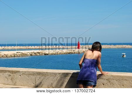 A woman in front of the sea - A woman while contemplating the sea of Trani deep in thought