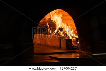 Pizza cooking brick oven with burning wood.