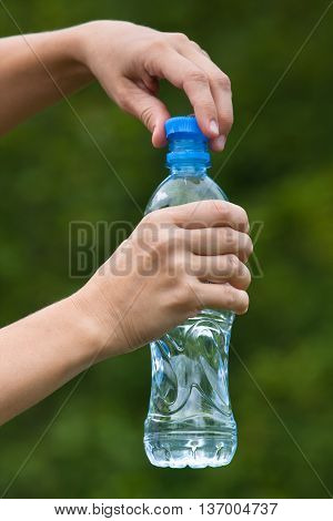 hands opening bottle with fresh water on nature background