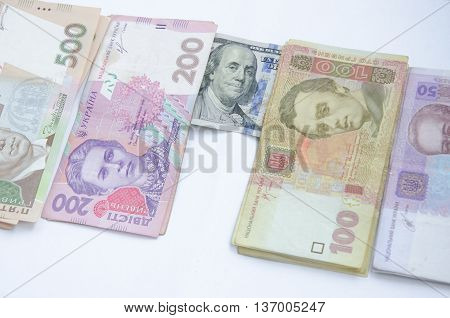 One hundred dollar bill on the background of ukrainian hryvnia