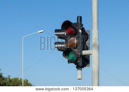 traffic light against a clear blue sky with lamp post in background