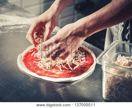 Chef cooking a gourmet tasty pizza close-up