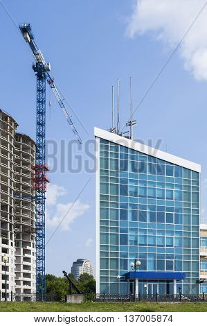 High-rise Building Under Construction And The Finished Office Building Against The Blue Sky.