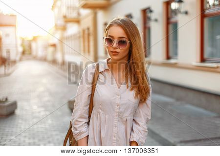 Stylish Beautiful Woman In Fashionable Clothes And Handbag With Sunglasses Standing At Sunset, Urban