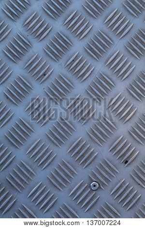 Non-slip industrial steel metal flooring, shot from above, flat lighting.