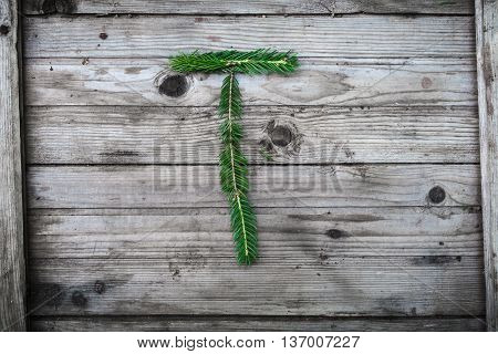 Letter T from fir tree branches on aged wooden boards