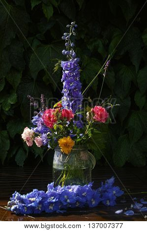 Sun after rain - colorful flowers bouquet in the garden with roses lavendel grape leaves and blue delfinium