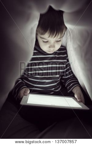 Cute little boy alone with tablet computer under blanket at night in a dark room