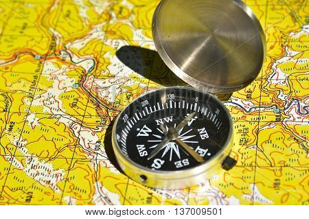 Map and compass - the tools for navigation. The magnetic compass lies on a topographic map.