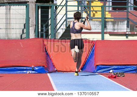 Young Woman Athlete Performs The High Jump Pole Vault