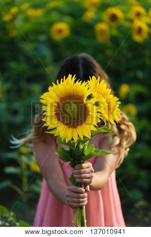 Young beautiful woman stands in a field of sunflowers a closed face