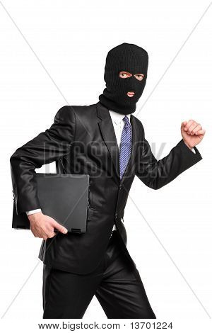 A Hacker In Robbery Mask Running With Laptop