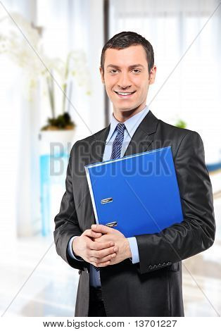 Happy Businessman With Blue Folder Posing In The Office