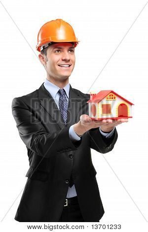 Smiling Foreman Wearing Helmet And Holding A Model House