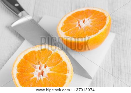 Ripe orange cut in two pieces on board with kitchen knife.