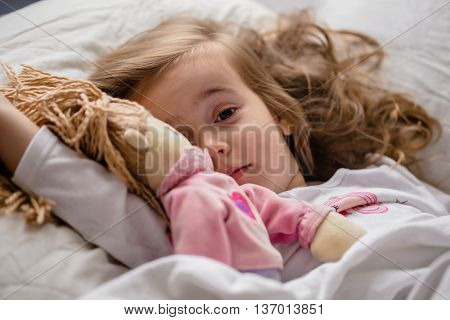 a little girl falls asleep in bed with soft doll white bed
