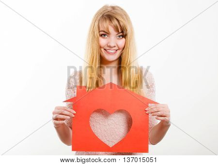 Love romance family future marriage concept. Smiling lady holding symbols. Gorgeous blonde shows house cutout with heart.