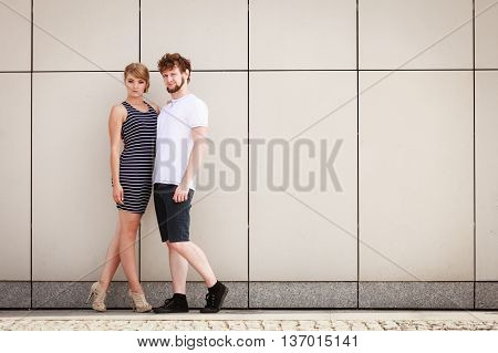 Sexy sensual couple posing outdoor. Pretty stunning woman in striped dress and handsome man in white shirt. Love and date concept.
