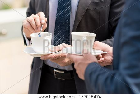 Relieve stress. Close up of cup of coffee in hands of pleasant man holding spoon and drinking beverage with his colleague