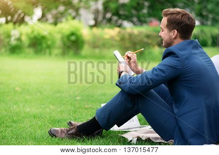 Keep your ideas in mind. Cheerful pleasant handsome man sitting on the grass and making notes