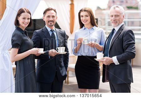 Enjoy the best taste. Cheerful delighted smiling colleagues drinking coffee and resting together while having a pleasant conversation