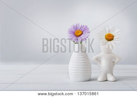 Beautiful aster amellus on white table at neutral background. Aster flower bouquet in white ceramic vase and camomile daisy in small vase in form of man. Floral friendship with copy space.