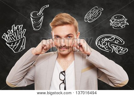 Handsome man and fast food temptation. Unhealthy food craving. Pizza, hamburger, hot dog, french fries and cola drink desire. Young guy with moustache and fast food drawing at black background