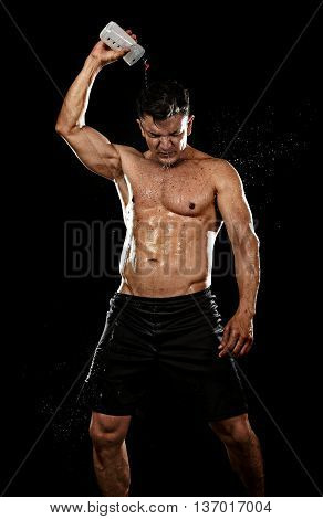 attractive strong sport man pouring water on his hair sweating tired after training hard on gym bodybuilding workout isolated on black background in health care hydration and fitness concept