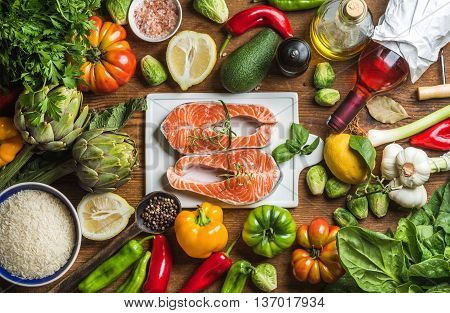 Dinner cooking ingredients. Raw uncooked salmon fish with vegetables, rice, herbs, lemon, artichokes, spices and bottle of rose wine on white ceramic board over wooden background, top view, horizontal composition