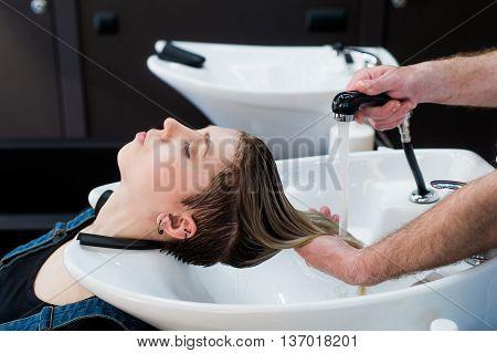 Beautiful woman getting a hair wash in a beauty salon.