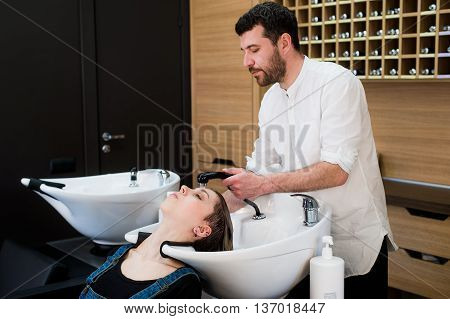 Handsome hairdresser washing female hair with concentration. He is holding a water tap. Woman leaning her head on sink
