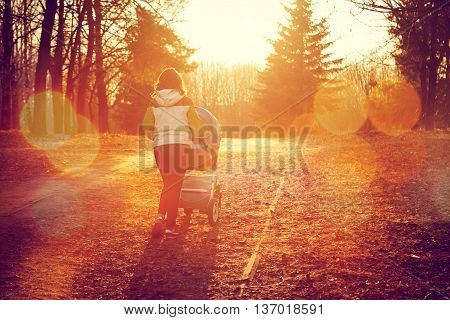 Mother with Baby Stroller Walking in Autumn Park and Enjoying Beautiful Sunset in Evening. Happy Parenting and Healthy Lifestyle Concept. Toned Photo with Bokeh and Copy Space.