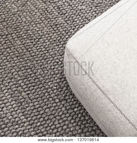 Close-up of a soft wool seat on gray carpet.