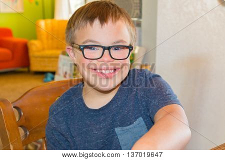 Young Boy With Downs Syndrome in Blue Shirt