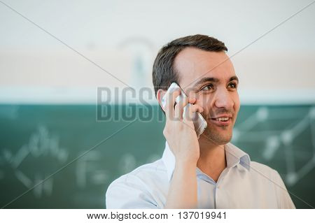 portrait closeup on a man talking phone at classroom in front of chalkboard.