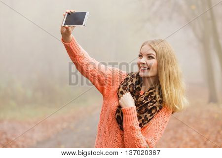 Happy fashion woman in fall autumn park taking selfie self photo picture. Pretty joyful young girl in sweater pullover with handbag photographing.