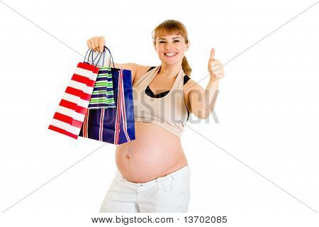 Happy pregnant woman holding shopping bags and showing thumbs up gesture isolated on white