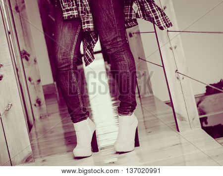 Casual clothing everyday fashion glamour garment. Closeup woman legs wear jeans high heels and flannel shirt.