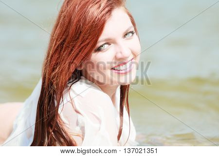 Vacation. Sensual girl wet cloth in water on the coast. Redhair woman having fun relaxing on the sea. Summertime.
