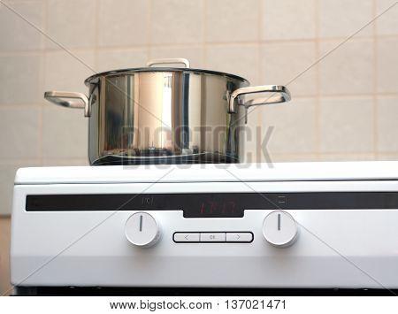 Metal steel saucepan with lid on modern kitchen electric stove. Photo closeup