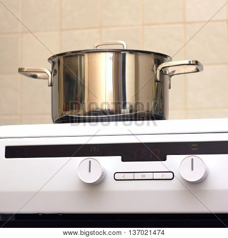 Metal steel saucepan with lid on new modern glass and ceramics kitchen electric stove. Photo closeup